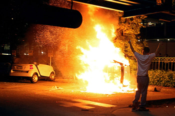 VANCOUVER, BC - JUNE 15:  A person walks in front of a burning vehicle on June 15, 2011 in Vancouver, Canada. Vancouver broke out in riots after their hockey team the Vancouver Canucks lost in Game Seven of the Stanley Cup Finals.  (Photo by Elsa/Getty Im