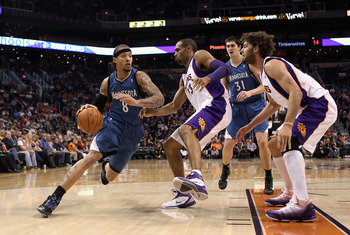 PHOENIX - DECEMBER 15:  Michael Beasley #8 of the Minnesota Timberwolves drives the ball agianst Grant Hill #33 of the Phoenix Suns during the NBA game at US Airways Center on December 15, 2010 in Phoenix, Arizona.  The Suns defeated the Timberwolves 128-