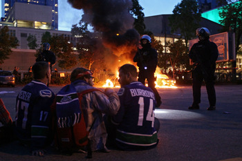 VANCOUVER, BC - JUNE 15:  Riot police stand in front of two burning police cars as people look on June 15, 2011 in Vancouver, Canada. Vancouver broke out in riots after their hockey team the Vancouver Canucks lost in Game Seven of the Stanley Cup Finals.