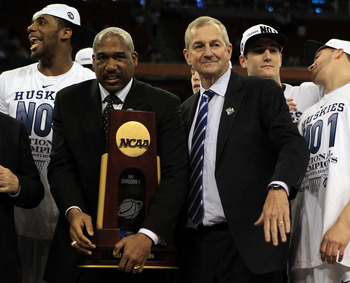 HOUSTON, TX - APRIL 04:  Athletic director Gene Smith of the Ohio State Buckeyes stands with head coach Jim Calhoun of the Connecticut Huskies as the Huskies celebrate with his team and the trophy after defeating the Butler Bulldogs to win the National Ch