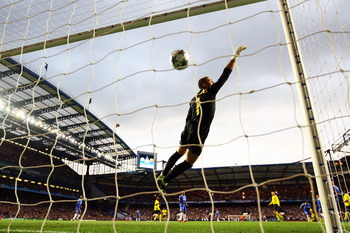 LONDON, ENGLAND - MAY 06:  Victor Valdes of Barcelona dives but can not stop the shot from Michael Essien of Chelsea scoring the first goal of the game during the UEFA Champions League Semi Final Second Leg match between Chelsea and Barcelona at Stamford