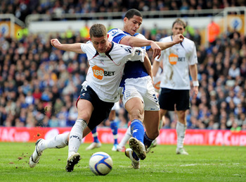 BIRMINGHAM, ENGLAND - MARCH 12:  Gary Cahill of Bolton Wanderers holds off a challenge from Curtis Davies of Birmingham City during the FA Cup sponsored by E.On Sixth Round match between Birmingham City and Bolton Wanderers at St Andrews on March 12, 2011