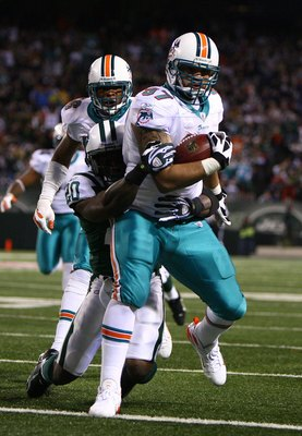 EAST RUTHERFORD, NJ - DECEMBER 28:  Phillip Merling #97 of The Miami Dolphins rumbles in for a touchdown after making an interception thrown by Brett Favre of The New York Jets during their game on December 28, 2008 at Giants Stadium in East Rutherford, N