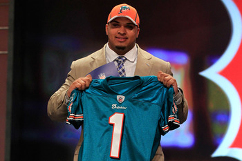 NEW YORK, NY - APRIL 28:  Mike Pouncey, #15 overall pick by the Miami Dolphins, holds up a jersey on stage during the 2011 NFL Draft at Radio City Music Hall on April 28, 2011 in New York City.  (Photo by Chris Trotman/Getty Images)