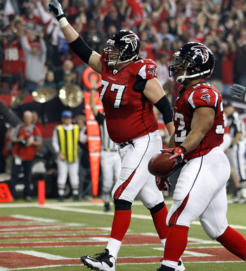 ATLANTA, GA - JANUARY 15:  (L-R) Tyson Clabo #77, Michael Turner #33 and Harvey Dahl #73 of the Atlanta Falcons celebrate after Turner scored a 12-yard rushing touchdown in the first quarter against the Green Bay Packers during their 2011 NFC divisional p