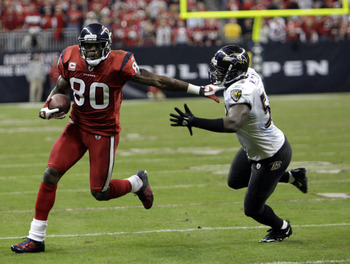 HOUSTON, TX - DECEMBER 13:  Wide receiver Andre Johnson #80 of the Houston Texans fends off  linebacker Jameel McClain #63 of the Baltimore Ravens as he gains a first down late in the fourth quarter at Reliant Stadium on December 13, 2010 in Houston, Texa