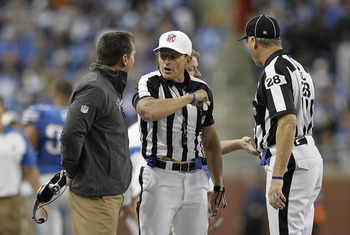DETROIT - DECEMBER 05: Detroit Lions head coach Jim Schwartz argues an Unnecessary Roughness call on Ndamukong Suh #90 by NFL referee Ed Hochuli #85 during the fourth quarter of the game against the Chicago Bears at Ford Field on December 5, 2010 in Detro