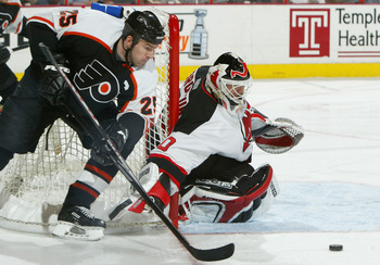 PHILADELPHIA - APRIL 10:  Keith Primeau #25 of the Philadelphia Flyers looks to control the puck in front of goalie Martin Brodeur #30 of the New Jersey Devils as the Flyers defeated the Devils 3-2 during game two of round one of the NHL Stanley Cup Playo