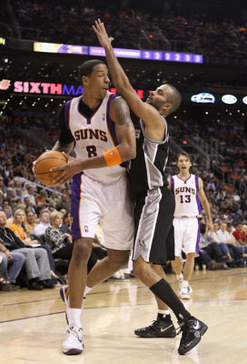 PHOENIX, AZ - APRIL 13:  Channing Frye #8 of the Phoenix Suns handles the ball under pressure from Tony Parker #9 of the San Antonio Spurs during the NBA game at US Airways Center on April 13, 2011 in Phoenix, Arizona.  NOTE TO USER: User expressly acknow
