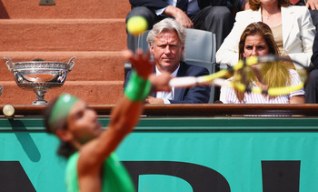 PARIS - JUNE 08:  Rafael Nadal of Spain serves as former player Bjorn Borg looks on during the Men's Singles Final match against Roger Federer of Switzerland on day fifteen of the French Open at Roland Garros on June 8, 2008 in Paris, France.  (Photo by M