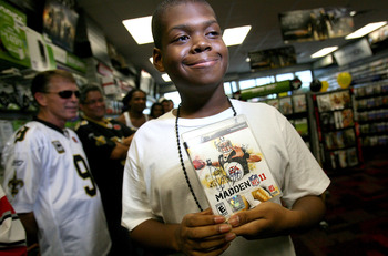 NEW ORLEANS - AUGUST 09: A very happy Ryan Jones, of New Orleans holds the first purchaced Madden NFL 11 video game signed by Marshall Faulk on August 9, 2010 in New Orleans, Louisiana. The game featuring New Orleans Saints quarterback Drew Brees goes on