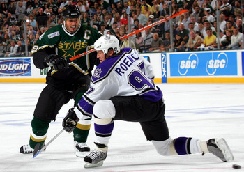 DALLAS - OCTOBER 5:  Center Mike Modano #9 of the Dallas Stars moves the puck past Jeremy Roenick #97 of the Los Angeles Kings on October 5, 2005 at the American Airlines Center in Dallas, Texas.  (Photo by Ronald Martinez/Getty Images)