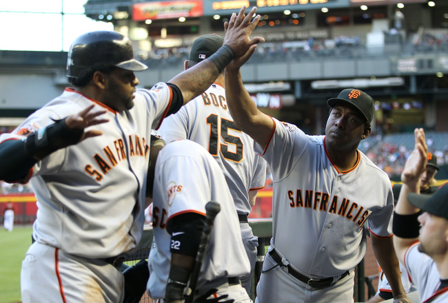 PHOENIX, AZ - JUNE 15:  Batting coach Hensley Meulens of the San Francisco Giants high fives Pablo Sandoval #48 after he scored a first inning run against the Arizona Diamondbacks during the Major League Baseball game at Chase Field on June 15, 2011 in Ph