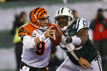 EAST RUTHERFORD, NJ - NOVEMBER 25:  Quarterback Carson Palmer #9 of the Cincinnati Bengals is tackled for a safety by Trevor Pryce #93 of the New York Jets at New Meadowlands Stadium on November 25, 2010 in East Rutherford, New Jersey. The Jets defeated t