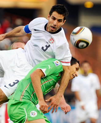 PRETORIA, SOUTH AFRICA - JUNE 23: Carlos Bocanegra of USA falls on top of Karim Matmour of  Algeria during the 2010 FIFA World Cup South Africa Group C match between USA and Algeria at the Loftus Versfeld Stadium on June 23, 2010 in Tshwane/Pretoria, Sout