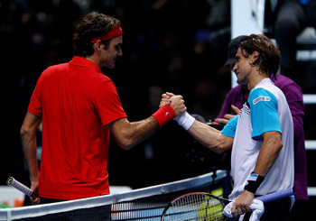 LONDON, ENGLAND - NOVEMBER 21:  Roger Federer of Switzerland (L) shakes hands with David Ferrer of Spain after defeating him during their men's singles first round match during the Barclays ATP World Tour Finals at O2 Arena on November 21, 2010 in London,