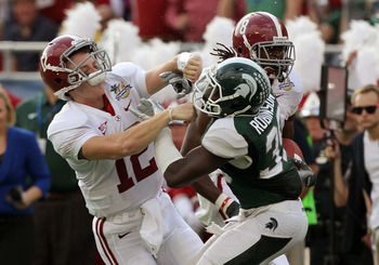 ORLANDO, FL - JANUARY 01:  Greg McElroy #12 of the Alabama Crimson Tide blocks Trenton Robinson #39 of  the Michigan State Spartans on a touchdown run during the Capitol One Bowl at the Florida Citrus Bowl on January 1, 2011 in Orlando, Florida.  (Photo b