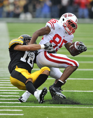 IOWA CITY, IA - OCTOBER 23- Defensive back Micah Hyde #18 of the University of Iowa Hawkeyes tackles wide receiver David Gilbreath #85 of the Wisconsin Badgers during the second half of play at Kinnick Stadium on October 23, 2010 in Iowa City, Iowa. Wisco