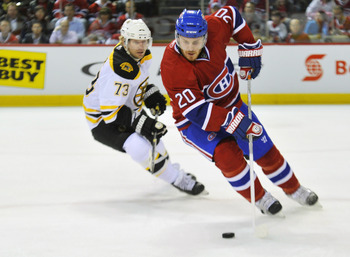 MONTREAL, QC - APRIL 18:  James Wisniewski #20 of the Montreal Canadiens turns up ice with the puck while being pursued by Michael Ryder #73 of the Boston Bruins in Game Three of the Eastern Conference Quarterfinals during the 2011 NHL Stanley Cup Playoff