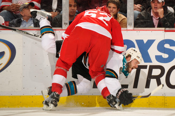 DETROIT - MAY 4:  Jonathan Ericsson #52 of the Detroit Red Wings checks Ian White #9 of the San Jose Sharks in the third period in Game Three of the Western Conference Semifinals during the 2011 NHL Stanley Cup Playoffs on May 4, 2011 at Joe Louis Arena i