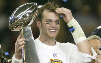 HOUSTON, TX - FEBRUARY 1:  MVP Tom Brady #12 of the New England Patriots raises the Lombardi trophy as he is interviewed by television commentator Jim Nance after defeating the Carolina Panthers 32-29 in Super Bowl XXXVIII at Reliant Stadium on February 1