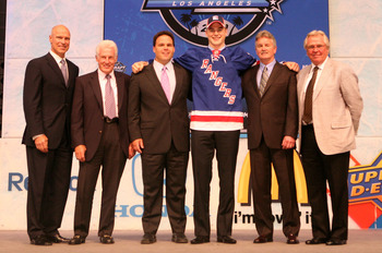 LOS ANGELES, CA - JUNE 25:  Dylan McIlrath, drafted tenth overall by the New York Rangers, poses on stage with team personnel during the 2010 NHL Entry Draft at Staples Center on June 25, 2010 in Los Angeles, California.  (Photo by Bruce Bennett/Getty Ima