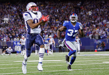 EAST RUTHERFORD, NJ - DECEMBER 29:  Randy Moss  #81 of the New England Patriots runs after a catch for his 23rd touchdown of the season breaking the all time season high for touchdowns in a season against James Butler #37 of the New York Giants on Decembe