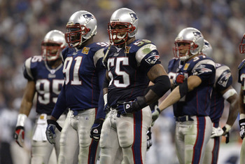 HOUSTON - FEBRUARY 1:  Defensive end Willie McGinest #55 of the New England Patriots stands next to defensive end Bobby Hamilton #91 in Super Bowl XXXVIII against the Carolina Panthers at Reliant Stadium on February 1, 2004 in Houston, Texas.  The Patriot
