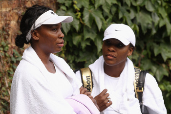 WIMBLEDON, ENGLAND - JUNE 18:  Venus Williams (L) and Serena Williams conclude their training session on the Aorangi Practice court at the All England Lawn Tennis and Croquet Club ahead of the Wimbledon Lawn Tennis Championships on June 18, 2011 in London