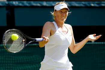 LONDON, ENGLAND - JUNE 28:  Maria Sharapova of Russia returns a shot during her match against Serena Williams of USA on Day Seven of the Wimbledon Lawn Tennis Championships at the All England Lawn Tennis and Croquet Club on June 28, 2010 in London, Englan