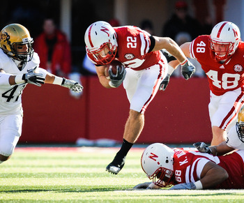 LINCOLN, NE - NOVEMBER 26: Rex Burkhead #22 of the Nebraska Cornhuskers leaps over teammate Keith Williams #68 and is helped by Tyler Legate #48 and Kyler Reed #25 of the Nebraska Cornhuskers during their game against the Colorado Buffaloes at Memorial St