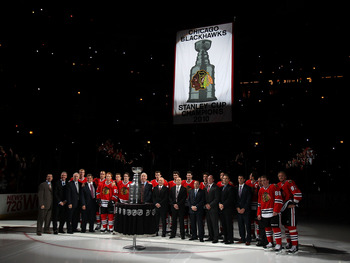 CHICAGO - OCTOBER 09: Members of the Chicago Blackhawks and their staff pose for a photo as the Stanley Cup Championship banner is raised during a ceremony before the Blackhawks season home opening game against the Detroit Red Wings at the United Center o