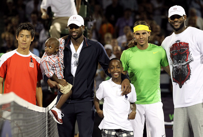 KEY BISCAYNE, FL - MARCH 26:  Miami Heat basketball players Dwyane Wade (2nd from L with sons Zion and Zaire) and LeBron James (R) pose for photo with Kei Nishhikori (L) of Japan and Rafael Nadal of Spain prior to their match during the Sony Ericsson Open