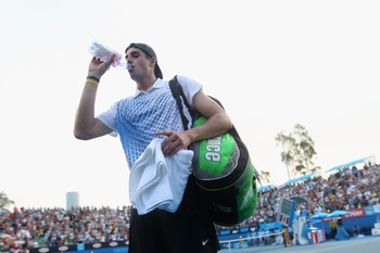 MELBOURNE, AUSTRALIA - JANUARY 22:  John Isner of the United States of America drinks a bottle of water as he leaves the court after losing to Marin Cilic of Croatia during their third round match on day six of the 2011 Australian Open at Melbourne Park o