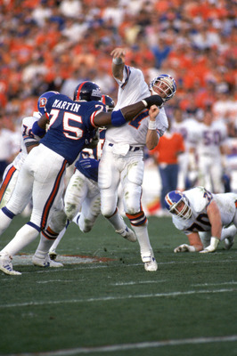 PASADENA, CA - JANUARY 25:  Quarterback John Elway #7 of the Denver Broncos gets rid of the ball just before getting hit by defensive end George Martin #75 of the New York Giants during Super Bowl XXI at the Rose Bowl on January 25, 1987 in Pasadena, Cali