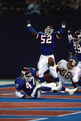 EAST RUTHERFORD, NJ - OCTOBER 28:  Linebacker Pepper Johnson #52 and safety Myron Guyton #29 of the New York Giants celebrate after the end zone interception by teammate Greg Jackson #47 during a game against the Washington Redskins at Giants Stadium Octo