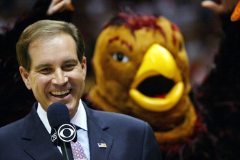 EAST RUTHERFORD, NJ - MARCH 27:  CBS analyst Jim Nantz shows a smile as the St. Joseph's Hawks mascot flaps his arms in the background before the start of the fourth round regional game of the NCAA Division I Men's Basketball Tournament against Oklahoma S