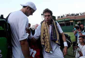 LONDON, ENGLAND - JUNE 23:  John Isner of USA (L) and Nicolas Mahut of France prepare to leave court 18 as light stops play at 59-59 in the last set on Day Three of the Wimbledon Lawn Tennis Championships at the All England Lawn Tennis and Croquet Club on