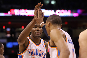 OKLAHOMA CITY, OK - MAY 23:  Kevin Durant #35 of the Oklahoma City Thunder reacts with teammate Russell Westbrook #0 in the first quarter against the Dallas Mavericks in Game Four of the Western Conference Finals during the 2011 NBA Playoffs at Oklahoma C