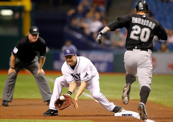 ST. PETERSBURG, FL - JUNE 18:  First baseman Casey Kotchman #11 of the Tampa Bay Rays takes the throw at first to get Logan Morrison #20 of the Florida Marlins for an out during the game at Tropicana Field on June 18, 2011 in St. Petersburg, Florida.  (Ph