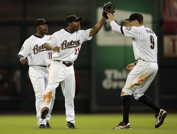 HOUSTON - AUGUST 31:  Center fielder Michael Bourn #21 and Jason Bourgeois #11 of the Houston Astros congratulate teammate Hunter Pence #9 after they defeated the St. Louis Cardinals 3-0 at Minute Maid Park on August 31, 2010 in Houston, Texas.  (Photo by