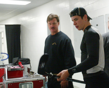 EAST RUTHERFORD, NJ - OCTOBER 5:  Sidney Crosby #87 (R) and trainer Steve Latin (L) of the Pittsburgh Penguins prepare Crosby's equipment for his first NHL game against the New Jersey Devils on October 5, 2005 at Continental Airlines Arena in East Rutherf