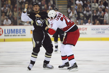 PITTSBURGH - OCTOBER 23:  Paul Bissonnette #16 of the Pittsburgh Penguins and Dan LaCouture #20 of the Carolina Hurricanes exchange punches during a first period fight on October 23, 2008 at Mellon Arena in Pittsburgh, Pennsylvania.  (Photo by Jamie Sabau