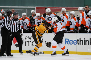 BOSTON - JANUARY 01:  Dan Carcillo #3 of the Philadelphia Flyers fights against Shawn Thornton #22 of the Boston Bruins as the refs and teammates look on during the first period of the 2010 Bridgestone Winter Classic at Fenway Park on January 1, 2010 in B