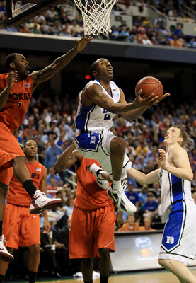 GREENSBORO, NC - MARCH 12:  Nolan Smith #2 of the Duke Blue Devils shoots against Terrell Bell #1 of the Virginia Tech Hokies as teammate Kyle Singler #12 looks on during the first half in the semifinals of the 2011 ACC men's basketball tournament at the