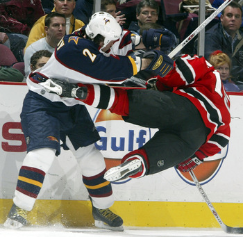 EAST RUTHERFORD, NJ - DECEMBER 23:   Defenseman Garnet Exelby #2 of the Atlanta Thrashers knocks down Jamie Langenbrunner #15 of the New Jersey Devils during their game at the Continental Airlines Arena on December 23, 2005 in East Rutherford, New Jersey.