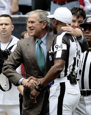 HOUSTON - OCTOBER 25:  Former President George W. Bush gives NFL referee Mike Carey a hug before the Houston Texans and Sa Francisco 49ers at Reliant Stadium on October 25, 2009 in Houston, Texas.  (Photo by Bob Levey/Getty Images)