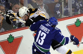 VANCOUVER, BC - JUNE 10:  Johnny Boychuk #55 of the Boston Bruins collides with Raffi Torres #13 of the Vancouver Canucks during Game Five of the 2011 NHL Stanley Cup Final at Rogers Arena on June 10, 2011 in Vancouver, British Columbia, Canada.  (Photo b