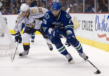 VANCOUVER, CANADA - APRIL 30: Chris Higgins #20 of the Vancouver Canucks handles the puck while being chased by Shane O'Brien #55 of the Nashville Predators during the second period in Game Two of the Western Conference Semifinals during the 2011 NHL Stan