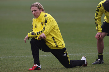 LIVERPOOL, ENGLAND - MARCH 16: Christian Poulsen of Liverpool stretches during a training session ahead of their UEFA Europa League Round of 16 second leg match against Braga at Melwood Training Ground on March 16, 2010 in Liverpool, England.  (Photo by C